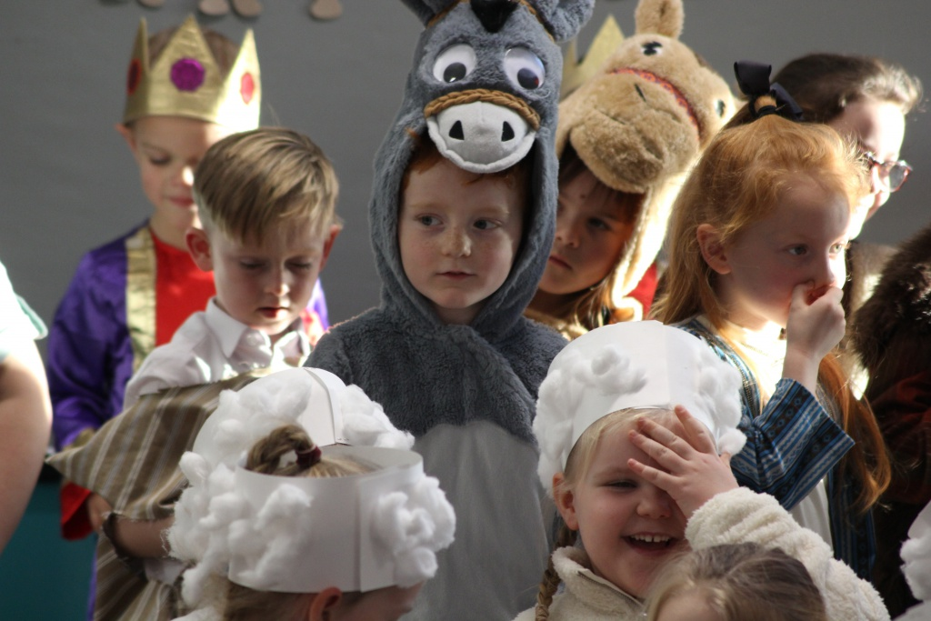 Group of children . Child in centre is dressed like a donkey